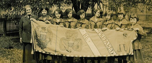 Juliette Gordon Low with girls holding banner